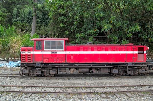 Der alte rote zug in der alishan-linie (bergab) kommt am nebligen tag zum bahnhof chiyi zurück.