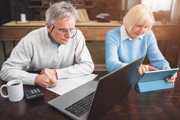 Der alte unternehmer und sein partner arbeiten zusammen an verschiedenen laptops
