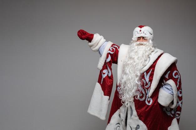 Der alte weihnachtsmann zeigt etwas von seiner hand, kopienraum
