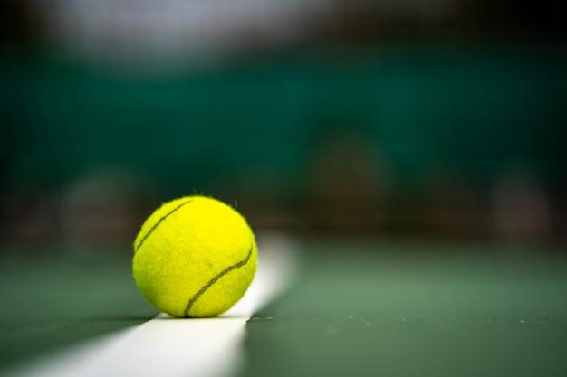Der anfang eines meisters, abschluss herauf tennisball auf dem gerichtshintergrund.