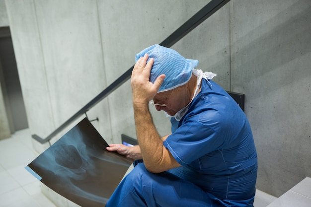 Der angespannte männliche chirurg untersucht die röntgenaufnahme auf der treppe