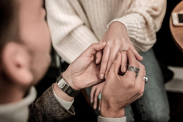 Der antrag. ein mann, der einen verlobungsring auf den finger der frau legt