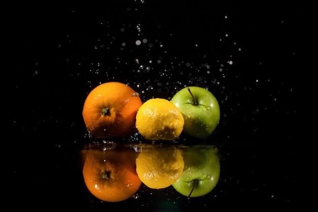 Der apfel, die orange und die zitrone stehen auf dem schwarzen hintergrund