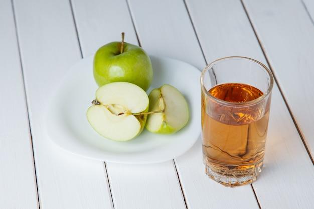 Der apfelsaft, der aus grünen äpfeln gießt, trägt in ein glas früchte