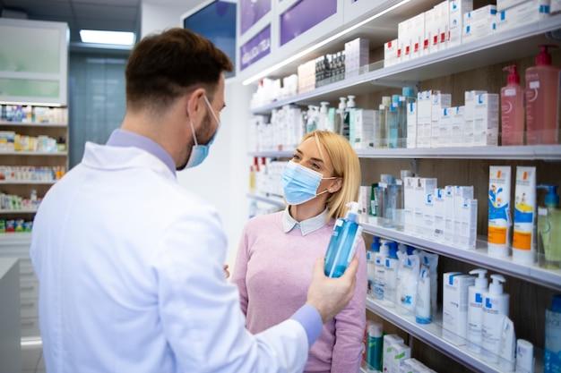 Der apotheker spricht mit dem kunden und berät, welches medikament er kaufen soll.