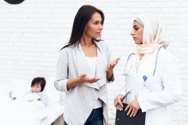 Der arabische arzt kommuniziert mit der mutter eines kranken jungen.