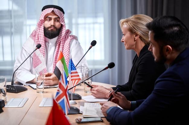 Der arabische scheich-manager hört aufmerksam einem der redner zu, die delegierte berichten, und wartet auf ideen für erfolgreiche investitionen in einem hellen, modernen büroraum. fokus auf kaukasische frau