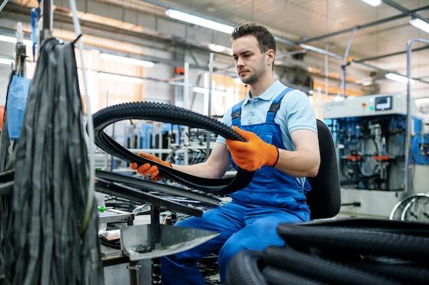 Der arbeiter an der montagelinie hält den fahrradreifen ab werk. produktion von fahrradrädern in der werkstatt, installation von fahrradteilen, moderne technologie