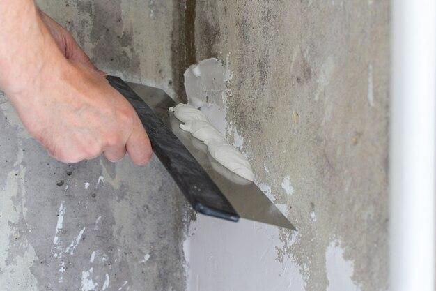 Der arbeiter bedeckt die unebenen wände, die hände des mannes mit einem großen spachtel und kitt, wohnungsreparatur