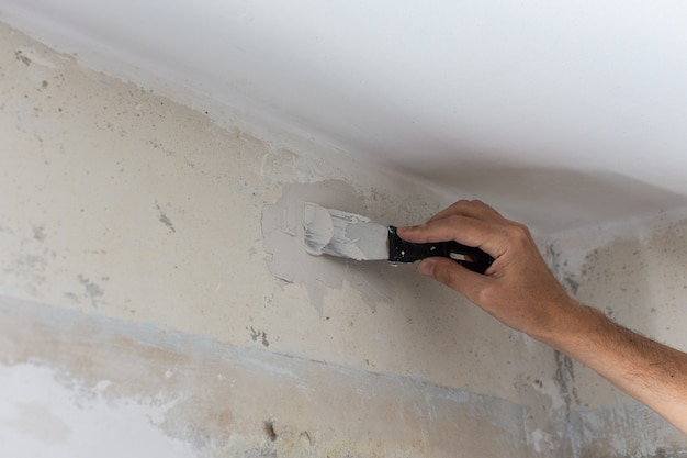Der arbeiter bedeckt die unebenen wände, die hände des mannes mit spachtel und kitt, wohnungsreparatur