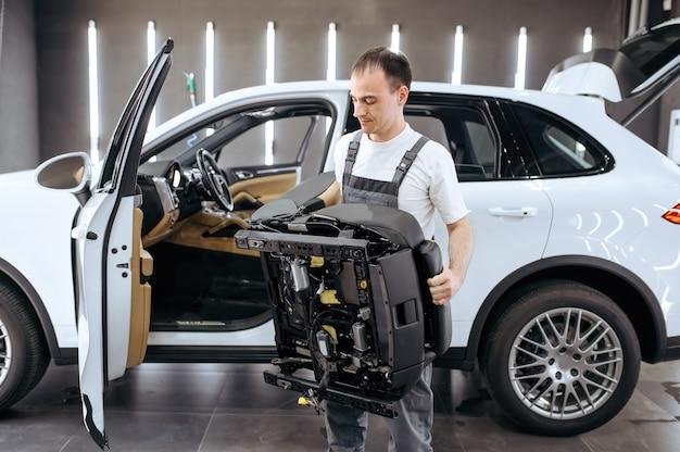 Der arbeiter hält den entfernten autositz zur chemischen reinigung und detaillierung fest