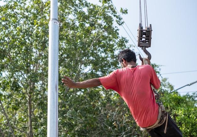 Der arbeiter hängt am kranwagen, um den strommast zu reparieren.