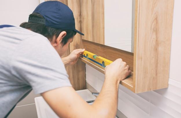 Der arbeiter installiert den spiegel im badezimmer