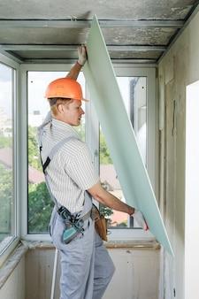 Der arbeiter installiert die trockenbauwand.