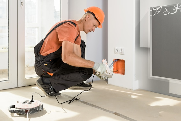 Der arbeiter installiert und schließt die stromversorgung der led-hintergrundbeleuchtung an.
