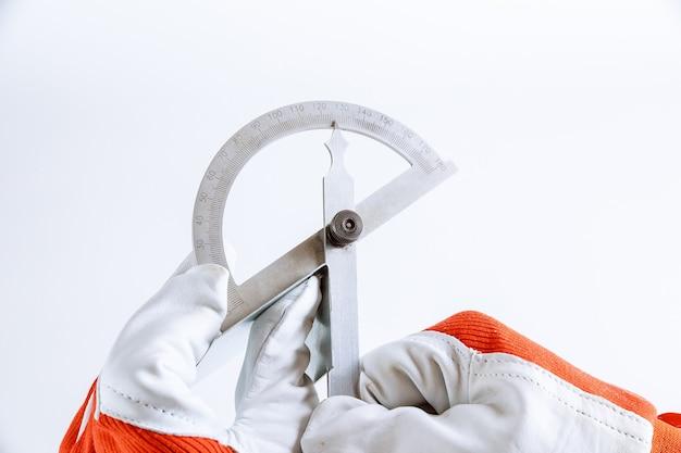 Der arbeiter misst den winkel auf dem metallprodukt mit einem digitalen winkelmesser