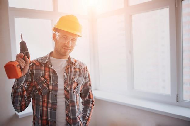 Der arbeiter oder baumeister hält eine elektrische bohrmaschine. bau- oder reparaturkonzept. vor dem hintergrund des bauens