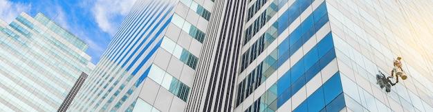 Der arbeiter putzt glasfenster am hochhaus mit dem hängenden seilkletterer