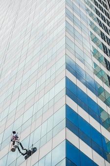Der arbeiter putzt mit dem hängenden seilkletterer das glasfenster im hochhaus. gebäudereinigungsservice für glasfenster.