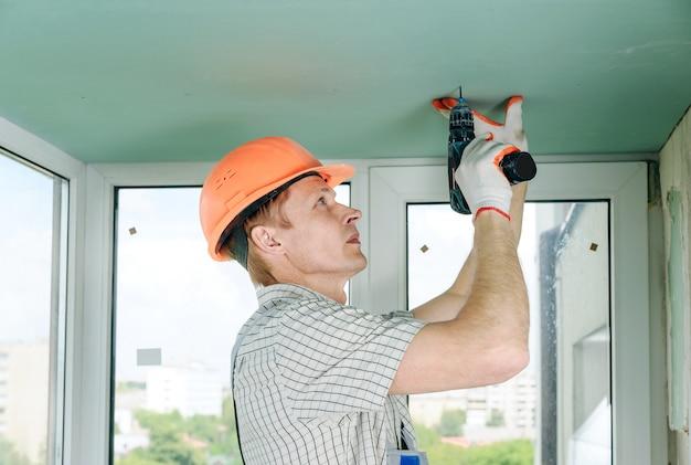 Der arbeiter repariert die trockenbauwand