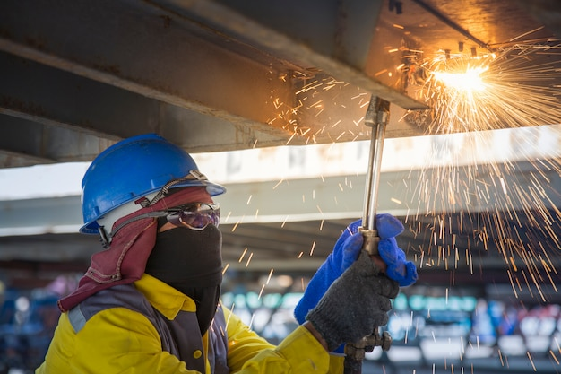 Der arbeiter schneidet die stahlbasis für den reparaturbehälter