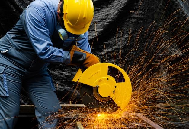 Der arbeiter schneidet metall mit einer elektrischen kreissäge. brunnen aus schleifenden metallfunken. metallbearbeitung mit personenschutzausrüstung.