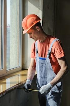 Der arbeiter überprüft die richtigkeit der installation eines fensterbretts.