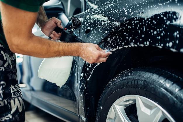 Der arbeiter verteilt seifenwasser und bereitet das auto auf den schutz vor spänen und kratzern vor.