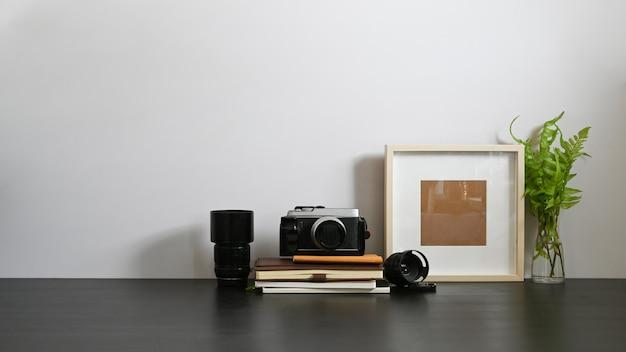 Der arbeitsbereich des fotografen ist von kamera, objektiv, bücherstapel, bilderrahmen und topfpflanze umgeben.
