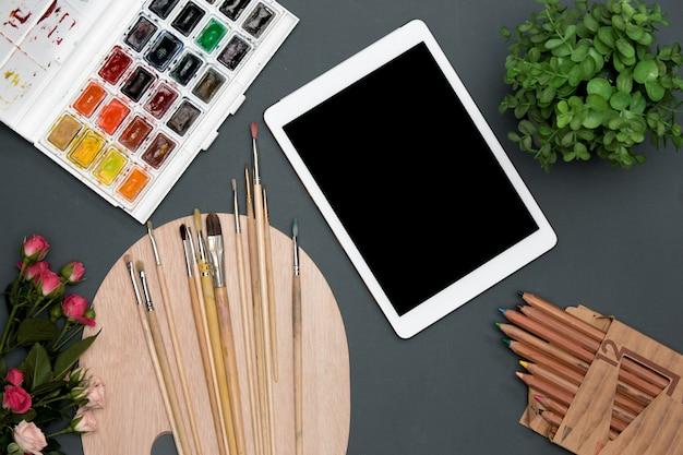 Der arbeitsbereich des künstlers mit laptop, farben, pinseln, blumen auf schwarz