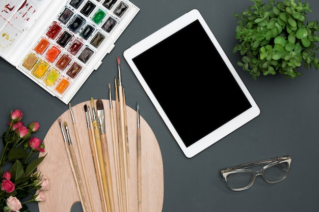 Der arbeitsbereich des künstlers mit laptop, farben, pinseln, blumen auf schwarzer oberfläche