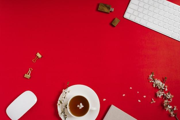 Der arbeitsplatz einer bloggerin mit computertastatur, büro, apfelbaumblumen, tee in einer tasse auf rotem grund. flache lage, ansicht von oben, kopienraum. frühlings- und valentinstagskonzept
