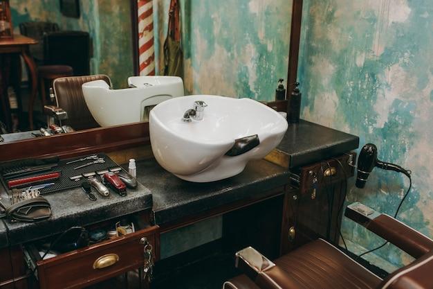 Der arbeitsplatz mit waschbecken im friseursalon. innenraum des luxusschönheitssalons.