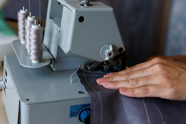 Der arbeitsprozess die näherin verarbeitet eine kante aus stoff-overlock