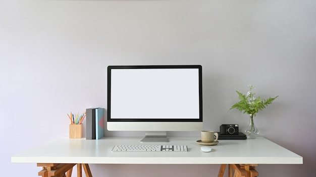 Der arbeitstisch ist von einem weißen computerbildschirm und bürogeräten umgeben