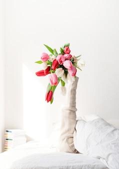 Der arm der frau streckte sich aus der decke und hielt einen strauß tulpenblumen. frau im bett, die tulpenblumen hält