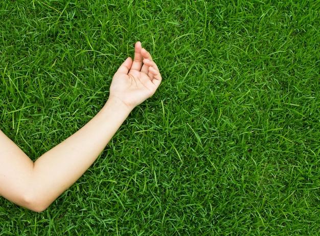 Der arm ruht auf grünem gras