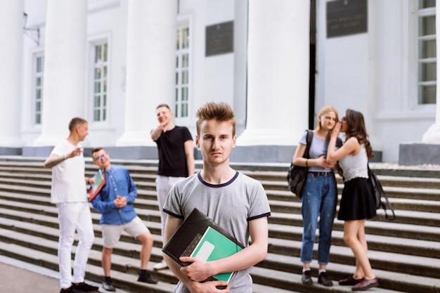 Der arme männliche student wird während der pause von seinen gruppenmitgliedern verspottet und verhöhnt