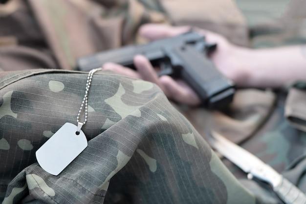 Der armeemarker liegt auf der tarnuniform des toten soldaten und der hand mit der pistole. konzept der kriegshandlungen zwischen der ostukraine und russland