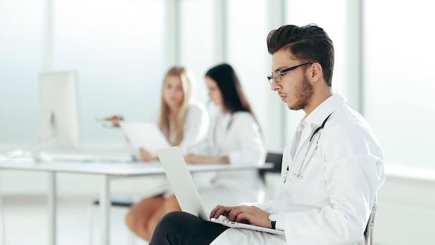 Der arzt arbeitet an einem laptop im krankenzimmer. foto mit speicherplatz