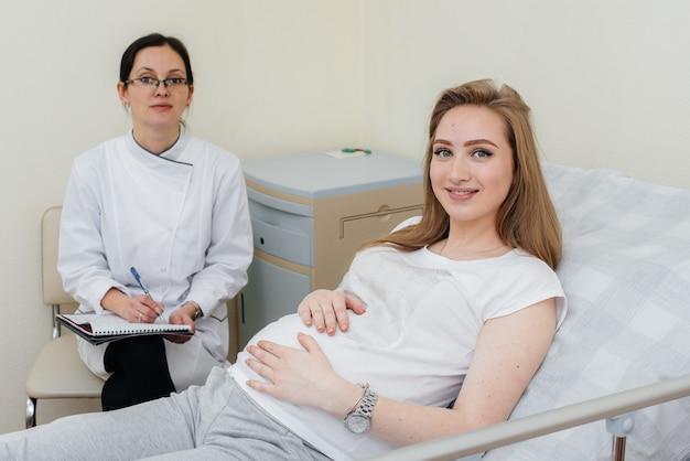 Der arzt berät und betreut ein junges schwangeres mädchen in einer medizinischen klinik. ärztliche untersuchung