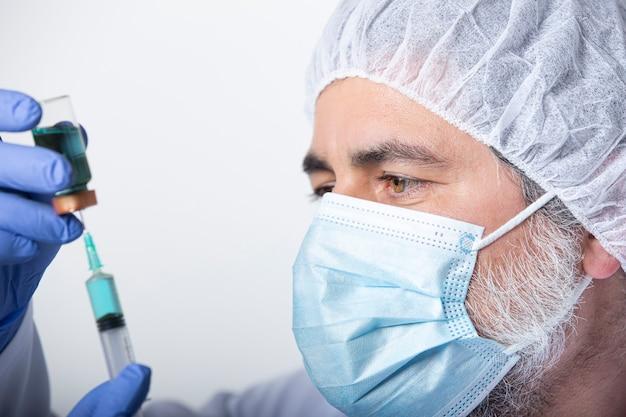 Der arzt bereitet den coronavirus covid-19-impfstoff für die spritze vor