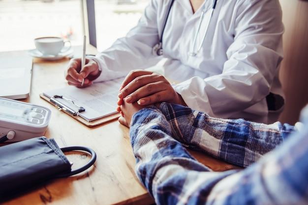 Der arzt bespricht mit dem patienten nach einer körperlichen untersuchung der ergebnisse und behandlungsrichtlinien.