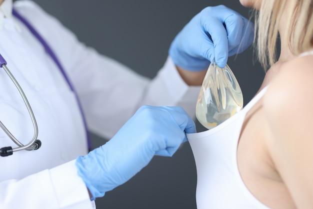 Der arzt, der das brustimplantat unter die patienten einführt, sinkt in nahaufnahme.