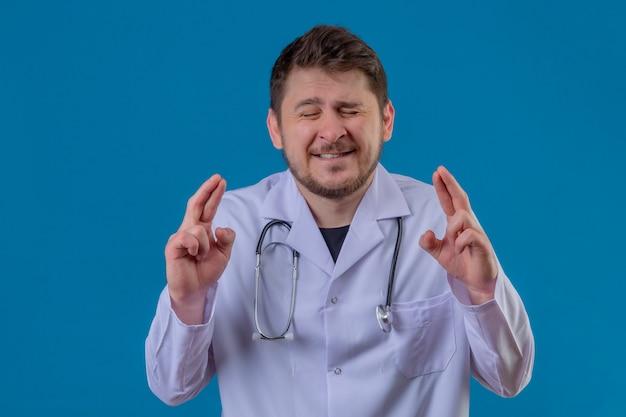 Der arzt des jungen mannes, der weißen kittel und stethoskop trägt, die mit geschlossenen augen stehen, die daumen drücken, macht wünschenswerten wunsch über isoliertem blauem hintergrund