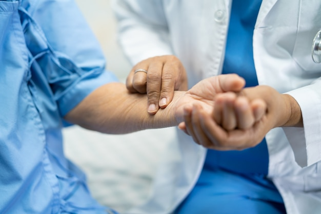 Der arzt fängt den puls mit dem patienten in der krankenstation, einem gesunden, starken medizinischen konzept.