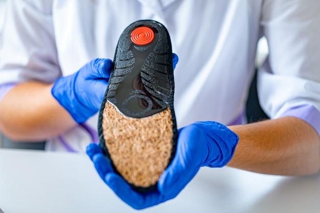 Der arzt für medizinische gummihandschuhe hält eine orthopädische innensohle zur behandlung und vorbeugung von plattfüßen während der ärztlichen beratung