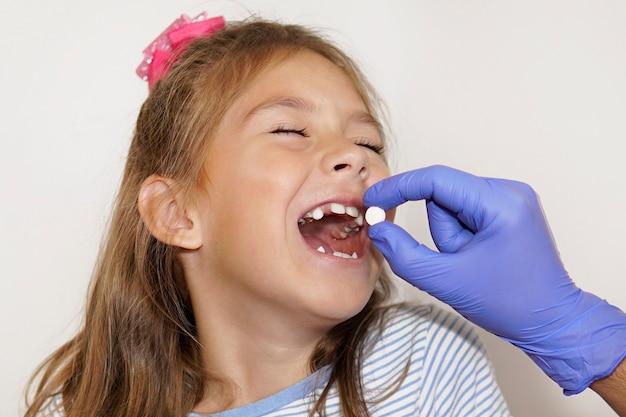 Der arzt gibt dem kind die pille in den offenen mund. eine krankenschwester gibt einem kleinen lächelnden mädchen medizin. behandlung von krankheiten im krankenhaus. das konzept der gesundheit