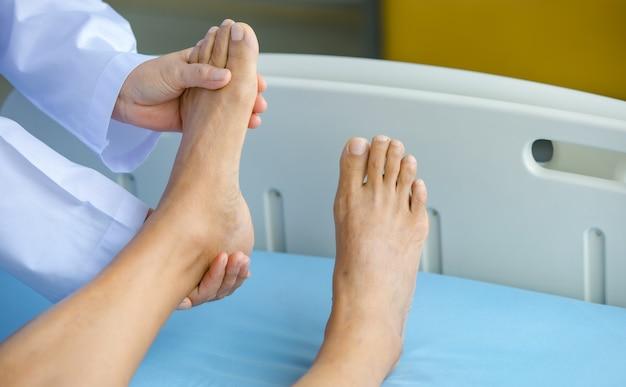 Der arzt hält den beinpatienten im krankenhaus auf dem bett und überprüft das nervensystem zur heilung und behandlung. konzept des guillain-barre-syndroms und der tauben handkrankheit oder der impfstoffnebenwirkung.