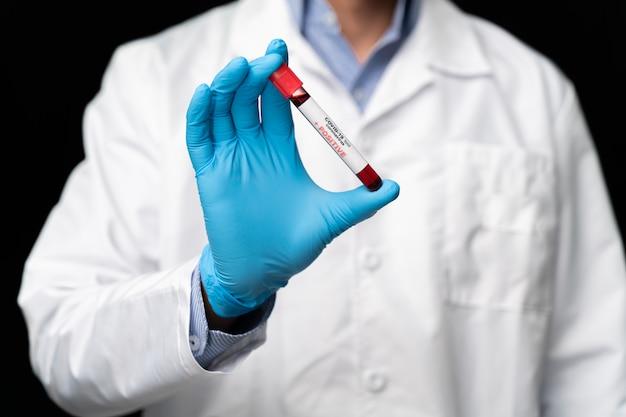 Der arzt hält den covid 19 coronavirus-impfstoff in der hand, die infizierte blutprobe im probenröhrchen, die impfstoff- und spritzeninjektion. er dient zur vorbeugung, immunisierung und behandlung von covid-19